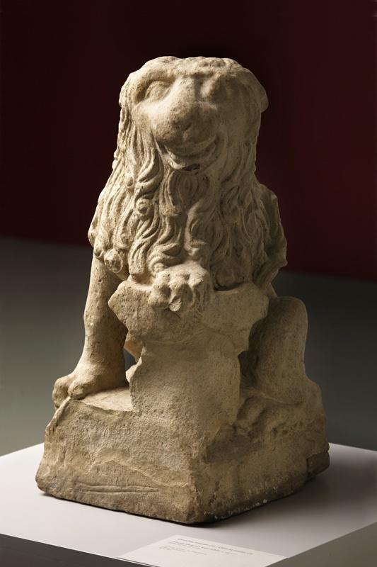 Zittende schilddragende leeuw