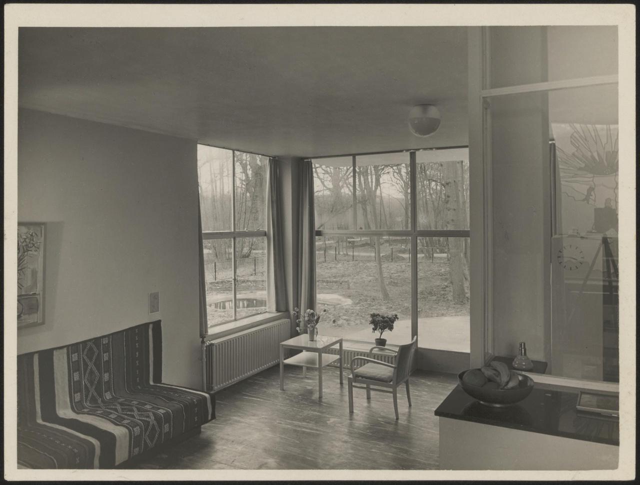 Afbeelding van woning Hillebrand, interieur woonkamer met hoekramen, stoel en tafeltje